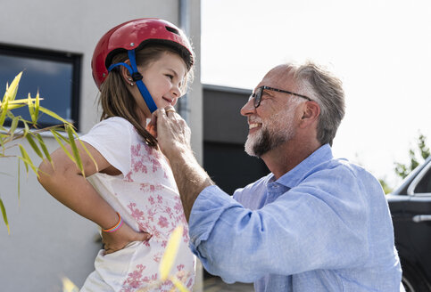 Mature man fixing safety helmet on little girl's head - UUF14563