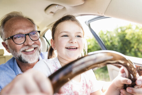 Little girl sitting on lap of grandfather, pretending to steer the car - UUF14566