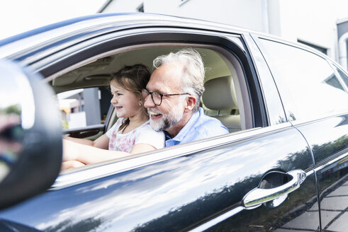Little girl sitting on lap of grandfather, pretending to steer the car - UUF14572