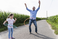 Grandfather and granddaughter playing with hoola hoop in the street - UUF14578