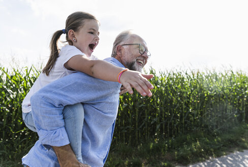 Grandfather carrying granddaughter piggyback - UUF14581
