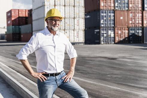 Businessman at cargo harbour, wearing safety helmet, portrait - UUF14584