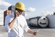 Businessman at cargo harbour, wearing safety helmet, using smartphone and digital tablet - UUF14593