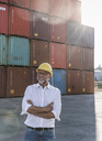 Businessman at cargo harbour, wearing safety helmet, arms crossed - UUF14605
