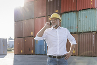 Businessman at cargo harbour, wearing safety helmet, using smartphone - UUF14608