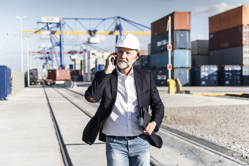 Businessman at cargo harbour, wearing safety helmet, using smartphone - UUF14611