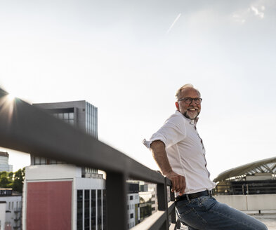 Mature man standing on roof of a high-rise building, leaning on railing - UUF14623