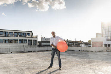 Mature man playing with orange fitness ball on rooftop of a high-rise building - UUF14632