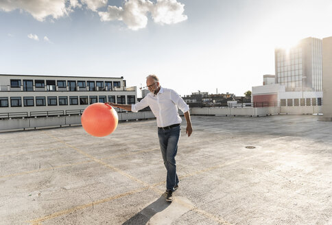 Mature man playing with orange fitness ball on rooftop of a high-rise building - UUF14635