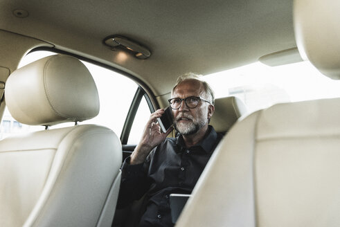 Mature businessman sitting on backseat in car, talking on the phone - UUF14638