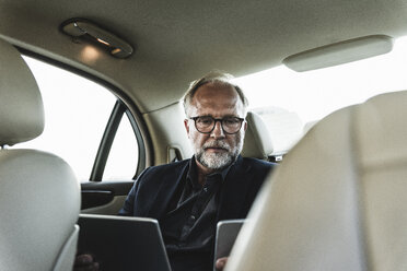 Mature businessman sitting on backseat in car, using digital tablet - UUF14641