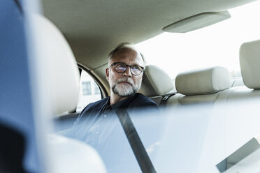 Mature businessman sitting on backseat in car, looking out of window - UUF14650