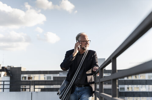 Mature man standing on rooftop, leaning on railing, using smartphone - UUF14653