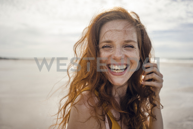 Portrait of a redheaded woman, laughing happily on the beach - KNSF04220 - Kniel Synnatzschke/Westend61