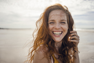 Portrait of a redheaded woman, laughing happily on the beach - KNSF04220