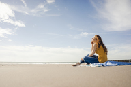 Woman sitting on the beach, enjoying the sun - KNSF04226