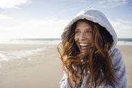 Woman having fun on a windy beach, wearing hood - KNSF04229