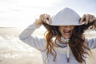 Woman having fun on a windy beach, wearing hood - KNSF04232