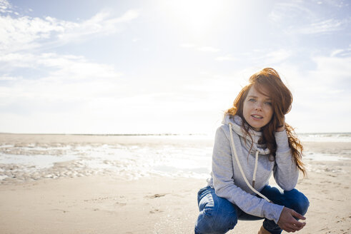 Redheaded woman relaxing on the beach, crouching - KNSF04238