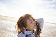 Redheaded woman enjoying fresh air at the beach - KNSF04244