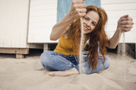 Redheaded woman sitting in front of beach cabin, with sand trickling through her hands - KNSF04256
