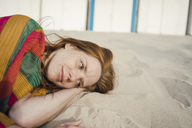 Redheaded woman resting in sand on the beach - KNSF04259