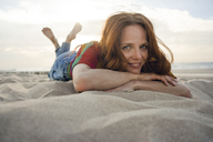 Redheaded woman lying in sand on the beach, smiling - KNSF04265