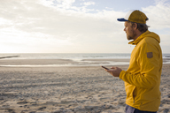 Man in yellow jacket, using smartphone on the beach - KNSF04271