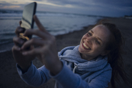 Woman using smartphone on the beach at sunset - KNSF04277