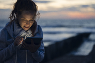 Woman using digital tablet on the beach at sunset - KNSF04280