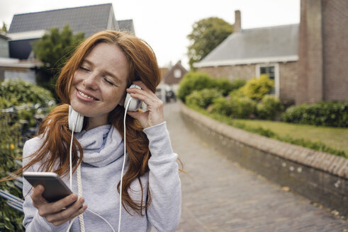 Redheaded woman using headphones and smartphone in the city - KNSF04286