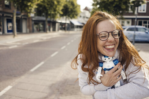 Redheaded woman hugging toy robot - KNSF04289