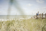 Woman sitting on fence at the sea, wearing headphones - KNSF04298