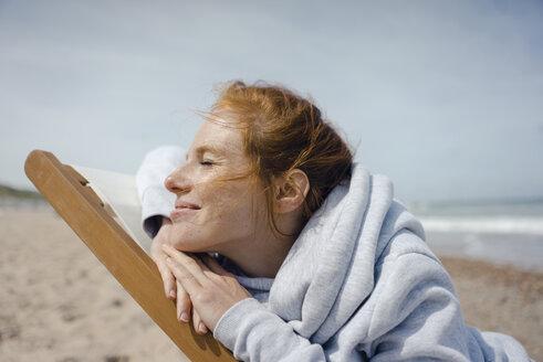 Smiling woman lying in deck chair, enjoying sunbath at the beach - KNSF04301