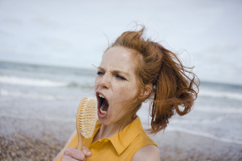 Woman using hair brush at the sea as a microphone - KNSF04304