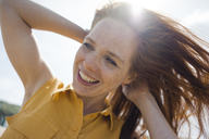 Portrait of a redheaded woman, laughing happily on the beach - KNSF04307