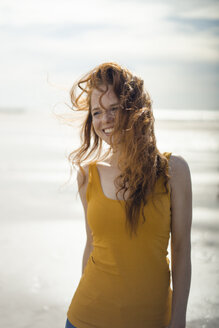 Portrait of a redheaded woman, laughing happily on the beach - KNSF04310