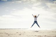 Happy woman having fun at the beach, jumping in the air - KNSF04325