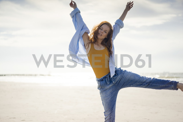 Happy woman having fun at the beach, jumping in the air - KNSF04328