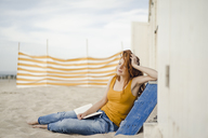 Redheaded woman sitting in front of beach cabin, reading a book - KNSF04331