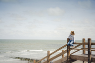 Woman sitting on fence at the beach, relaxing at the sea - KNSF04337