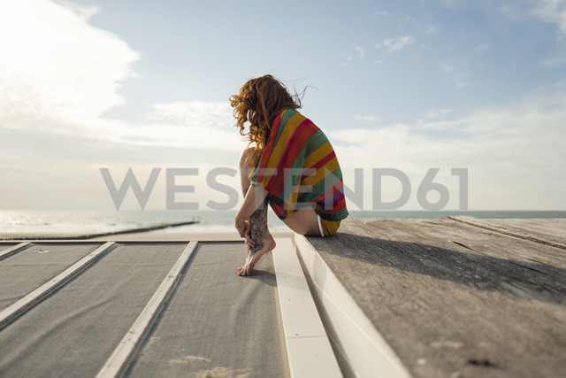 Woman with tattoo crouching on plank, looking at the sea - KNSF04343 - Kniel Synnatzschke/Westend61