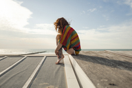 Woman with tattoo crouching on plank, looking at the sea - KNSF04343