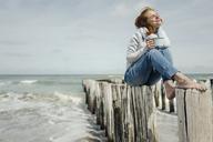 Woman sitting on fence at the sea, drinking tea - KNSF04346