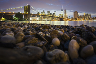 Night view towards Manhattan from Brooklyn, with the Brooklyn Bridge spanning the East River, the rocky shore in the foreground. - MINF01781