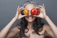 Mature woman covering eyes with red and yellow tomato - ISF16995
