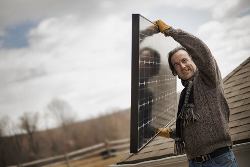 A man carrying a large solar panel across a farmyard. - MINF01846