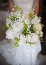 A woman in a white dress, a bride holding a bridal bouquet of white flowers, large white roses and peonies, with delicate yellow flowers and green leaves. - MINF02107