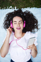 Portrait of young woman lying on blanket listening music with smartphone and pink headphones - ABIF00753