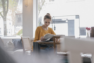 Young woman sitting in coworking space, reading newspaper - JOSF02318